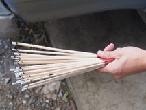 Burning incense sticks holding on a hand with waving smoking Stock Photos
