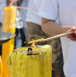 Burning incense sticks. On a yellow candle flame Stock Image