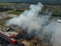 Burning industrial building. Smoke, collapsed roof aerial view stock images