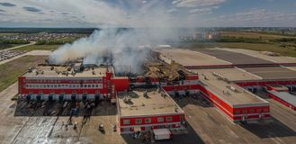 Burning industrial distribution warehouse, aerial drone view royalty free stock images