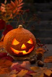 Burning Jack O'Lantern on a rustic table. With autumn decorations, darkly lit Stock Photo