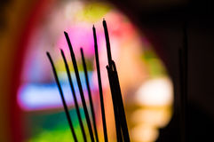 Burning of joss sticks in Chinese temple. Joss sticks are burned in front of a colorful background in a Chinese temple. Smoke and fragrance is rising into the Stock Photo