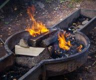 burning journaler Ovanlig form för fyrpanna Årsdag av en picknick royaltyfri fotografi