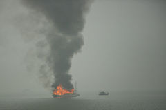 Burning junk boat in the sea Stock Photography