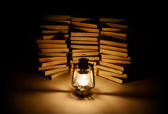 Burning kerosene lamp and books Royalty Free Stock Photo