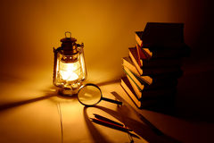 Burning kerosene lamp and books, concept light Stock Images