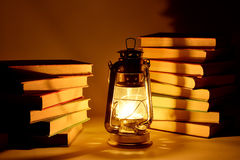 Burning kerosene lamp and books, concept light Royalty Free Stock Images
