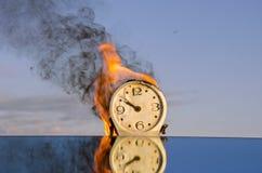 Burning klockavisartavla - tidsymbol Arkivfoto