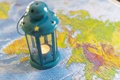 The burning lamp is blue On the map. Inside the lamp, the candle is burning white Stock Photography