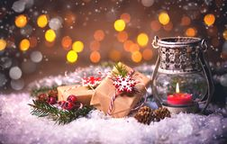 Burning lantern and gift boxes in the snow Stock Photo