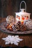 Burning lantern, pine cones and Christmas-tree decorations Royalty Free Stock Image