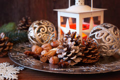 Burning lantern, pine cones and Christmas-tree decorations Stock Images