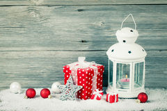 Burning lantern in the snow with christmas decoration. On wood background Royalty Free Stock Photo