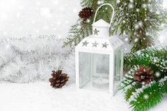 Burning lantern, spruce branches with cones, tinsel and snow Stock Photo