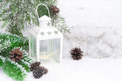 Burning lantern, tree branches and Christmas tinsel Royalty Free Stock Images