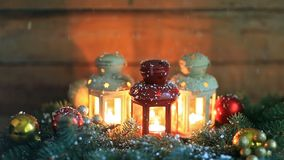 Burning lanterns with Christmas decoration and falling down real snowflakes. In slow motion stock footage