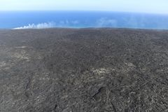 Helicopter aerial view of lava entering the ocean and steam, Big Island, Hawaii. A burning lava flow is seen pouring over rock and into the ocean. Steam can be Royalty Free Stock Photo