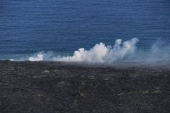 Helicopter aerial view of lava entering the ocean and steam, Big Island, Hawaii. A burning lava flow is seen pouring over rock and into the ocean. Steam can be Stock Image