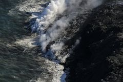 Helicopter aerial view of lava entering the ocean and steam, Big Island, Hawaii. A burning lava flow is seen pouring over rock and into the ocean. Steam can be Royalty Free Stock Image