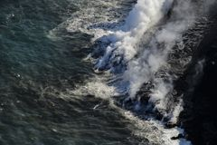 Helicopter aerial view of lava entering the ocean and steam, Big Island, Hawaii. A burning lava flow is seen pouring over rock and into the ocean. Steam can be Royalty Free Stock Images