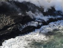 Helicopter aerial view of lava entering the ocean and steam, Big Island, Hawaii. A burning lava flow is seen pouring over rock and into the ocean. Steam can be Stock Photos