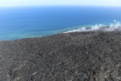 Helicopter aerial view of lava entering the ocean and steam, Big Island, Hawaii. A burning lava flow is seen pouring over rock and into the ocean. Steam can be Stock Photography