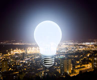 The burning light bulb on the background lights of the night cit Stock Images