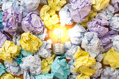 Burning light bulb among crumpled paper sheets Royalty Free Stock Photo