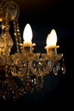 A burning light bulb on a crystal chandelier on a dark backgroun Royalty Free Stock Images
