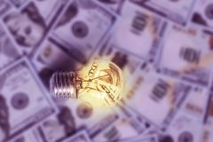 Burning light bulb on dollars background, expensive electricity. The burning light bulb on dollars background, expensive electricity Royalty Free Stock Image