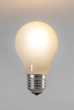 Burning light bulb. On a gray background Stock Image