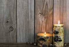 Burning log candles by acorns and old distressed wood background Royalty Free Stock Photos