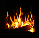 Burning log and fire. On black Royalty Free Stock Image