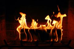 Burning log in the fireplace. Burning fire log lighting the fireplace and heating a house Royalty Free Stock Images