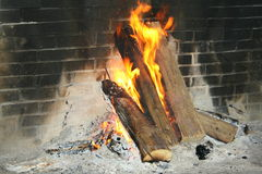 Burning logs in an open fireplace. Large open fireplace with burning logs Royalty Free Stock Photo
