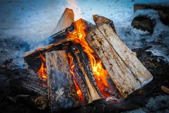 Burning logs in a snowy winter with smoke stock images