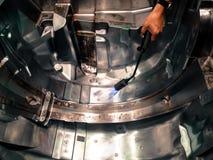 Burning manual del hombre asiático del técnico en la superficie del molde de acero Imagen de archivo