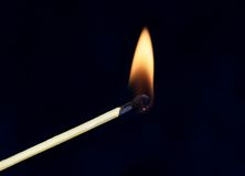 Burning match. Closeup of a burning match.  Black background Stock Image