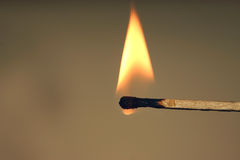 Burning match. A burning match on a brown background royalty free stock photography