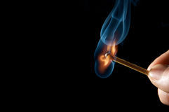 Burning match. Isolated on black background Stock Images