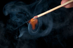 Burning match. Isolated on black background Royalty Free Stock Photography