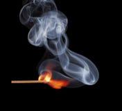 Burning match on black background Stock Photos