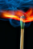 Burning match with blue smoke. Over black background Royalty Free Stock Image