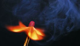 Burning match flame. A burning match with flame and smoke against a black background Royalty Free Stock Photos