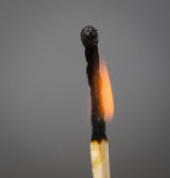 Burning match on a gray Royalty Free Stock Image