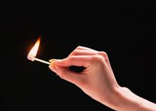 A burning match in a hand. A match in hand,burning.Bright point in the dark Royalty Free Stock Image