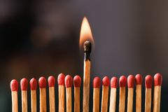Burning match among others on black background. Difference and uniqueness concept Royalty Free Stock Photos