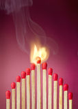 Burning match setting fire to its neighbors Royalty Free Stock Images