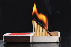 Burning matches in a box. Burning matches in a box on a black background Stock Images