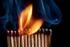 Burning matchstick. On black background Stock Photos